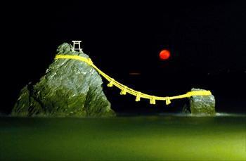 夫婦岩の真ん中から昇った満月に近い月=2011年12月12日、三重県伊勢市二見町