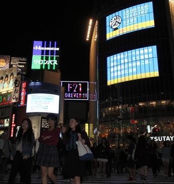 大型LEDビジョンが並ぶスクランブル交差点では、日本人3氏のノーベル賞受賞のニュースも映し出された=7日夜、東京都渋谷区、川村直子撮影