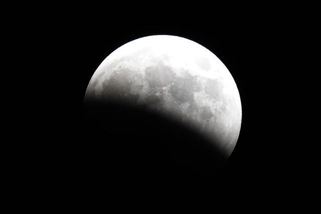 始まった月食=8日午後6時44分、東京都中央区、白井伸洋撮影