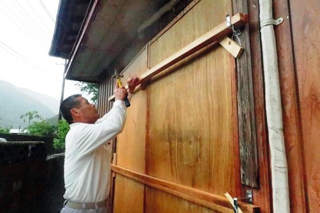 暴風に備え、自宅の窓に板をはる住民。周辺では2010年の豪雨災害で2人が犠牲になった=2014年10月11日、鹿児島県奄美市住用町