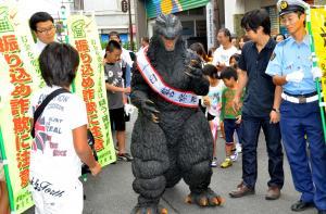 一日警察署長として商店街を練り歩いたゴジラ=高知県香美市