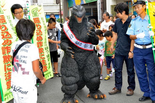 一日警察署長として商店街を練り歩いたゴジラ=2014年9月20日、高知県香美市