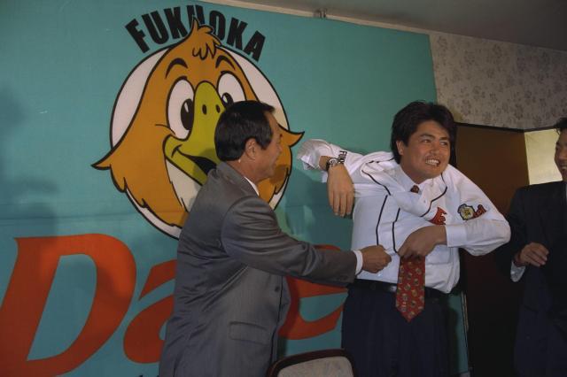 入団会見後にダイエーのユニホームを着る工藤投手=1994年12月7日の朝日新聞