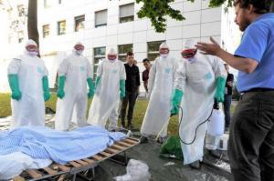 エボラ出血熱対策の訓練。防護服に身をくるんだ参加者が、講師(右)の指示を聞きながら、消毒液を感染者のベッド周辺に噴霧する練習をした=2014年9月16日日、スイス・ジュネーブの国際赤十字・赤新月社連盟本部、松尾一郎撮影