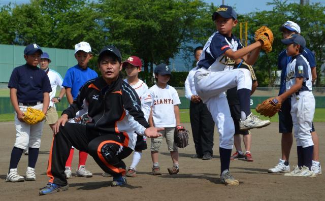 子どもに投球フォームを指導する工藤公康さん=2012年7月1日の朝日新聞