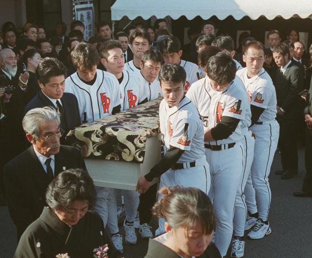 藤井選手の棺を運ぶダイエーの選手とともに、喪服姿の巨人・工藤選手の姿もあった=2000年10月17日の朝日新聞