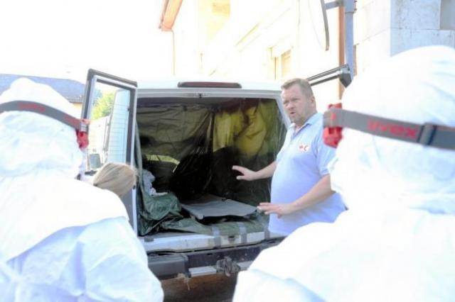 エボラ出血熱対策の訓練。防護服に身をくるんだ参加者が、簡易な救急車でエボラ出血熱患者を搬送する際の注意点を講師から学んだ=2014年9月16日、スイス・ジュネーブの国際赤十字・赤新月社連盟本部、松尾一郎撮影