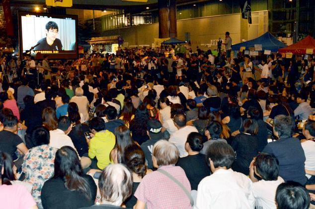 占拠の続く香港の官庁街・金鐘では香港政府と民主派の対話が大型スクリーンで同時中継され、学生団体の代表が発言する姿が映し出されると大きな拍手があがった=石橋亮介撮影