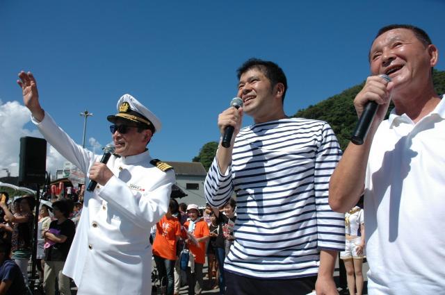 海上パレードでヨットに手を振るタモリさん(左)=沼津市