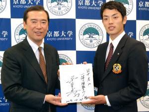 ロッテ伊東監督の直筆サインの色紙を持つ京大の田中(右)。左はロッテの林球団本部長=2014年10月24日、京都市左京区