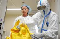 防護服を脱いだ看護師(左)。着脱を手伝う看護師も防護服を着用する=2014年10月24日、名古屋市昭和区の名古屋第二赤十字病院