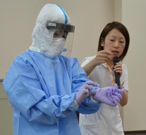 防護具着脱のデモンストレーション。看護師は「できるだけ露出がないように」と説明した=2014年10月23日、下関市長府外浦町の関門医療センター