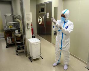 防護服を慎重に脱ぐ看護師。使用済みの防護服などは部屋にある機械(中央)で加熱処理される=22日午後4時48分、札幌市中央区の札幌市立病院、恵原弘太郎撮影