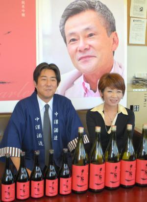 完成した純米吟醸酒「秀一」をPRする中村佳代さん(右)と中沢一洋さん。後ろのポスターは池田秀一さん=2014年10月7日