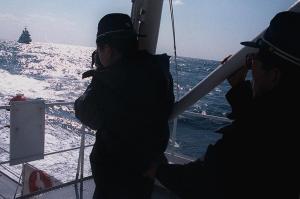 荒れる海上で、資料用に韓国船を撮影する「なつぐも」の乗組員=長崎県・対馬沖で=1998年2月10日