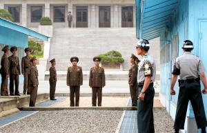 休戦ラインぎりぎりの場所に立ち警備にあたる北朝鮮軍兵士に、少し離れてヘルメット姿の韓国軍兵士(右側2人)が向き合う=2006年10月11日