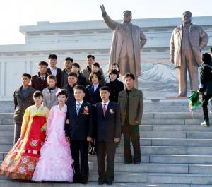 万寿台の丘に建つ金日成主席(左)と金正日総書記の銅像には、結婚式に臨むカップルが「あいさつのため」続々と献花に来ていた。ガイドの案内で、記者団も見学した=2014年10月28日、平壌