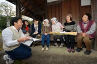 調査結果を住民に説明する生徒たち(左から3人)。住民のひざの上にあるのが納豆を巻く藁束=紀美野町花野原