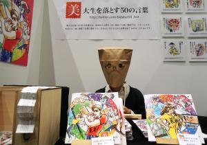 デザインフェスタのブースで、紙袋をかぶったコスチュームでガイドブックを販売する渋谷さん=2014年11月9日、東京ビッグサイト