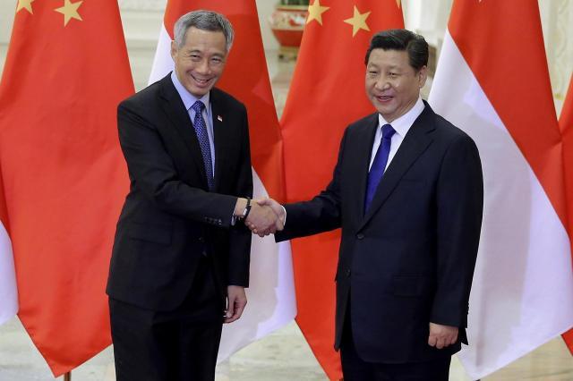 習近平国家主席と握手するシンガポールのリー・シェンロン首相=2014年11月9日