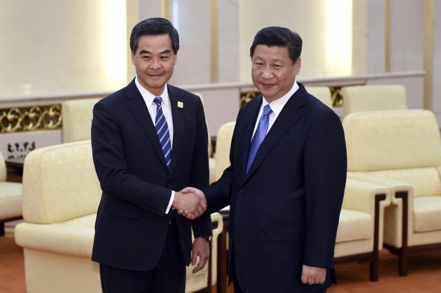 習近平国家主席と握手する香港の梁振英行政長官=2014年11月9日