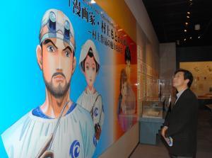 「村上もとか展」に掲げられた「JIN―仁―」の看板を眺める作者の村上もとかさん=2010年12月23日