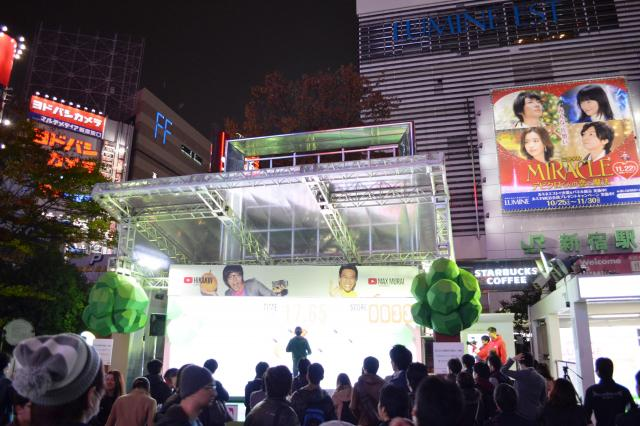 新宿駅東口前のゲーム会場。人だかりの中、ステージ上で跳んだり走ったりしている人がいます=11日、東京・新宿で