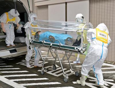 エボラ出血熱に備えた大阪府の訓練で、防護服を着て患者を搬送する保健所職員=2014年11月17日
