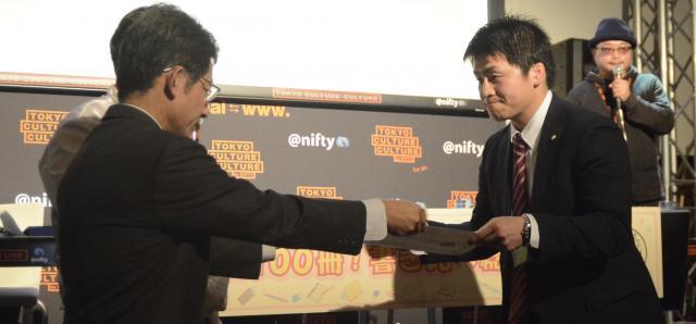 表彰状を受け取る不二精機の青木太志さん(右)=東京・お台場