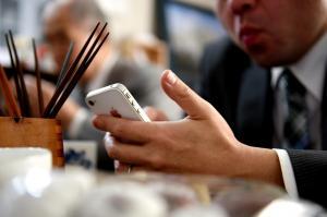 昼食休憩中にツイッターで投稿する候補者=2014年12月2日、東京都内、白井伸洋撮影