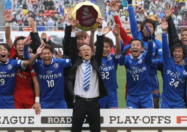J1復帰を決め、田坂監督がトロフィーを掲げ、喜ぶ大分の選手ら=2012年11月23日、関田航撮影