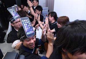iPhoneのかぶり物をし、店員とハイタッチをする来店者=2014年9月19日、大阪市北区、加藤諒撮影