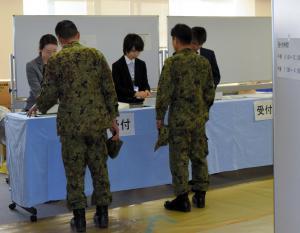 不在者投票所の受付で投票手続きをする陸上自衛隊員=2014年12月8日、埼玉県和光市役所