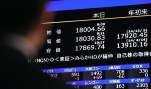 日経平均が1万8000円を超えたことを伝える株価ボードを見る人=2014年12月8日、大阪市中央区北浜、竹花徹朗撮影