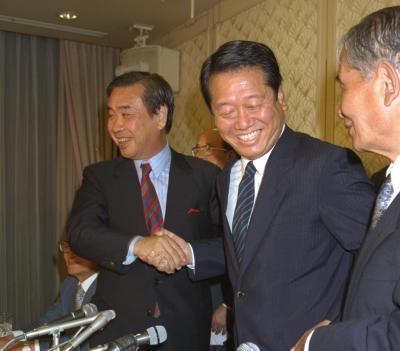総選挙で55議席を獲得、笑顔で握手する新生党の羽田孜党首(左)と小沢一郎代表幹事=1993年7月19日