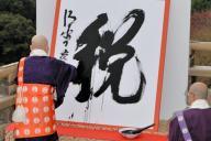 今年の漢字「税」を墨書する清水寺の森清範貫主=12月12日午後、京都市東山区