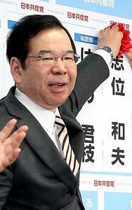 当選を決め、花をつける共産党の志位和夫委員長