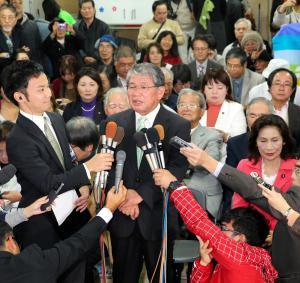 当選を決め、インタビューに答える赤嶺政賢氏(中央)=2014年12月14日
