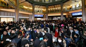 JR東京駅で、開業100周年記念の「Suica」が途中で販売中止となり、駅員に問い合わせる人たちでごった返した=2014年12月20日