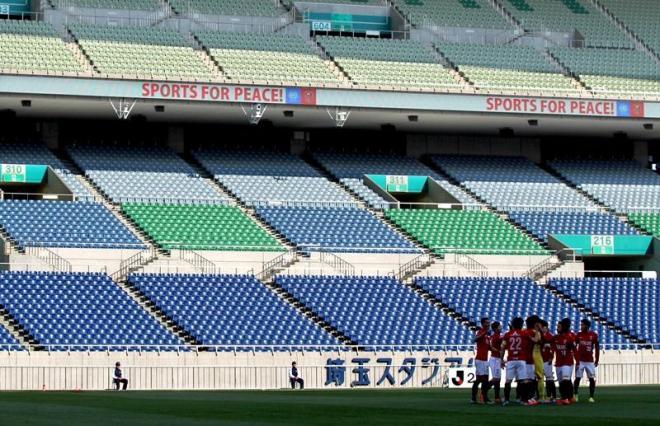 観客のいないスタンドをバックに円陣を組んで試合に臨む浦和の選手たち=23日午後3時3分、さいたま市緑区の埼玉スタジアム、上田潤撮影