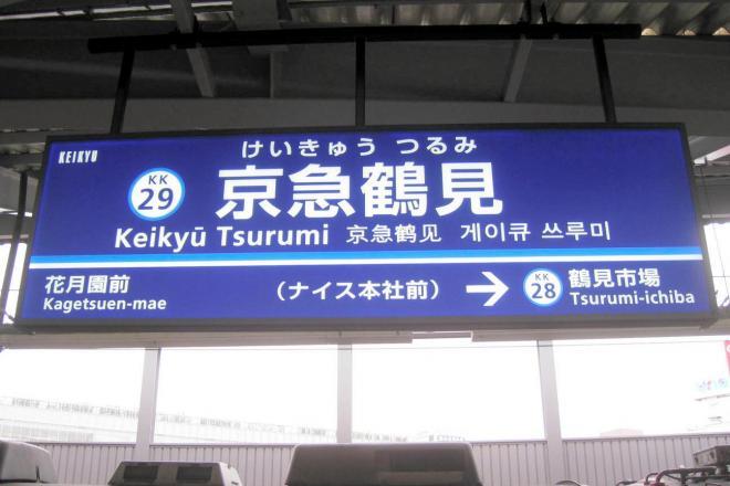 「ナイス本社前」の副駅名称が表示された京急鶴見駅の駅看板。もう一つの駅名を付けるにはどうすれば?