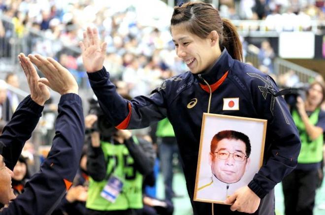父栄勝さんの遺影を持ち、ハイタッチする吉田沙保里選手=16日午後、東京都板橋区、長島一浩撮影