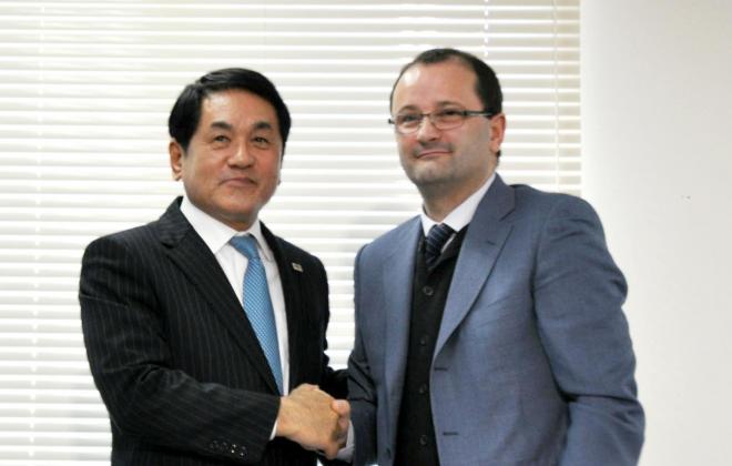 会見後、日本協会の梅野副会長(左)と握手をするFIBAのバウマン事務総長=12月18日、東京都品川区