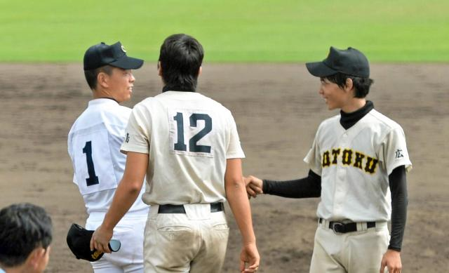 あいさつした後に握手を交わす中京の松井投手(1)と崇徳の石岡投手=兵庫県の明石トーカロ球場
