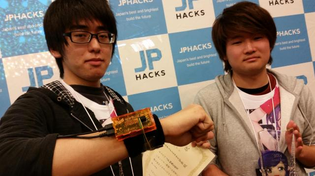 最優秀賞は会津大2年の五十嵐太清さん(19、左)と坂口勇太さん(20)。腕につけた機器「スピリチュアル握手」で握手するだけでスマートフォンに相手の名刺情報を送信する
