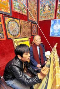 国・チベット自治区ラサ中心部のチベット宗教画「タンカ」の店を見学する丹羽宇一郎氏=2011年8月20日