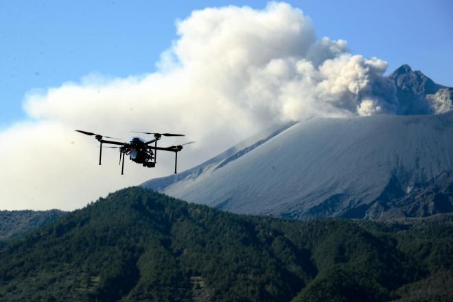 テスト飛行で桜島を上空から撮影する無人飛行機「ドローン」、日本では防災分野での活用が進んでいる