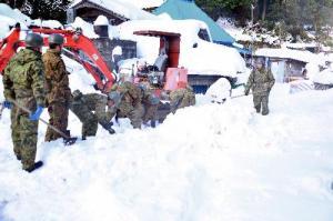 重機が入らず手作業で雪かきをする自衛隊員=2014年12月9日、徳島県三好市