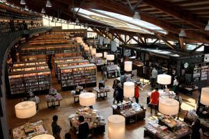 武雄市図書館。手前の平積みは販売ゾーンで、右奥にはスターバックスの店舗がある