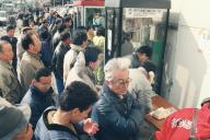 1995年の阪神淡路大震災で公衆電話の横に設置された災害用の臨時電話に列を作る人たち